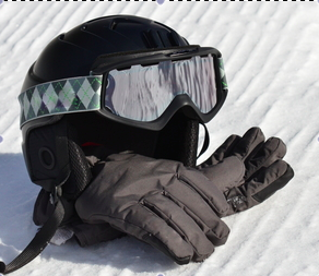 Gloves and helmet pictured on snow