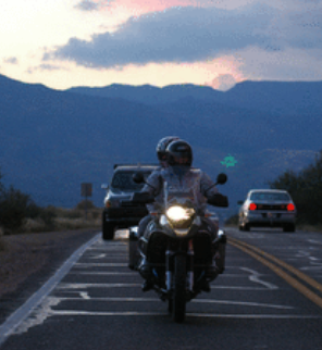 Two riders on the road at dusk